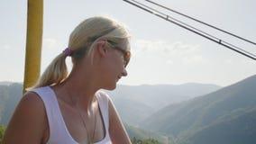 Un turista feliz de la mujer está montando en el remonte en el verano Días de fiesta en las montañas en la estación de verano almacen de metraje de vídeo