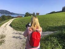 Un turista femenino toma una foto en el campo Foto de archivo libre de regalías