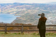 Un turista femminile che per mezzo del suo smartphone per catturare la bella l Fotografia Stock