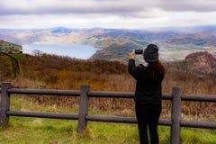 Un turista femminile che per mezzo del suo smartphone per prendere Mountain View della foto Fotografie Stock Libere da Diritti