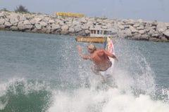 Un turista hace un truco que practica surf en la playa de Lagos fotos de archivo