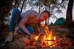 Un turista joven está soplando un fuego imagenes de archivo
