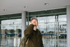 Un turista masculino joven en el aeropuerto o cerca de un centro comercial o de una estación llama un taxi o habla en un teléfono Imagen de archivo