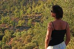 Un turista mira las colinas cubiertas con los olivos en Creta fotos de archivo