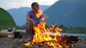 Un turista se sienta por el fuego en la orilla de un lago de la montaña almacen de video