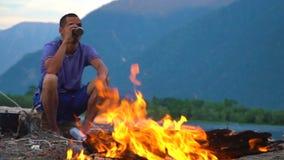 Un turista se sienta por el fuego en la orilla de un lago de la montaña metrajes