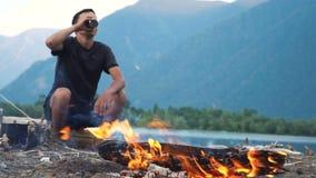 Un turista se sienta por el fuego en la orilla de un lago de la montaña almacen de metraje de vídeo