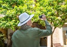 Un turistico, portando un cappello e una sciarpa, fotografie un arancio w Immagini Stock Libere da Diritti