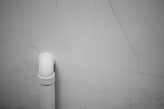 Un tuyau blanc attaché sur un mur blanc avec la fracture photos stock
