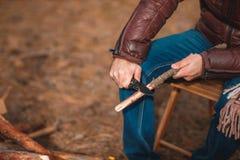 Un type affile un bâton en bois avec un couteau Plan rapproché photographie stock