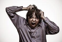 Un type asiatique de bureau soumet à une contrainte à sa limite dans le gru lourd de grain Photos stock