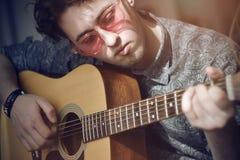 Un type aux cheveux boucl?s avec les verres roses joue une m?lodie en bois de guitare acoustique images libres de droits