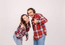 Un type avec une fille dans des écouteurs montre deux doigts et une langue sur un fond gris Photographie stock