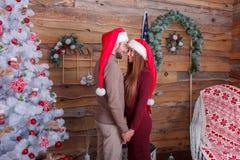 Un type avec une fille avec des sourires dans des chapeaux du ` s de nouvelle année est se tenant prêt et tenant des mains dans u Photos libres de droits