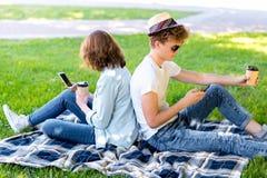 Un type avec une fille en été détendent en nature Il tient un smartphone dans des ses mains et lit la correspondance Il tient a Photographie stock