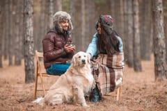 Un type avec une fille s'assied sur des chaises avec un chien dans la forêt d'automne Image stock