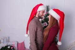 Un type avec une fille se tiennent l'un à côté de l'autre regardant le fond d'un arbre de Noël Images stock