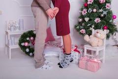 Un type avec une fille tenant des mains et regardant l'un l'autre Montrant seulement des pieds et des mains ensemble Image libre de droits