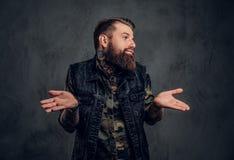 Un type barbu élégant avec les mains tatouées dans le gilet militaire de chemise et de denim posant avec un regard perplexe Photo photos libres de droits