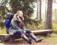 Un type barbu avec des sacs à dos se reposant dans le camp de forêt, aventure, Image stock