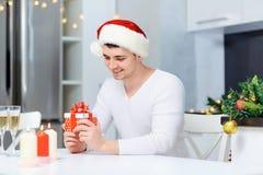 Un type dans un chapeau de Santa Claus avec un cadeau à une table dans Noël Photographie stock libre de droits