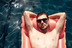 Un type dans des lunettes de soleil flotte sur un matelas gonflable dans la piscine Photo stock