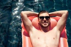 Un type dans des lunettes de soleil flotte sur un matelas gonflable dans la piscine Photographie stock libre de droits