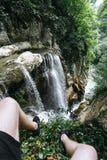 Un type dans des shorts noirs et des espadrilles s'assied au bord d'une roche devant une grande cascade en gorge d'Agur Photos libres de droits