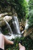 Un type dans des shorts noirs et des espadrilles s'assied au bord d'une roche devant une grande cascade en gorge d'Agur Image libre de droits