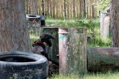 Un type dans des vêtements de camouflage avec des armes dans des ses mains jette un coup d'oeil par derrière un baril de fer Jeu  photographie stock