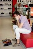 Un type dans le magasin choisit des chaussures Photographie stock libre de droits