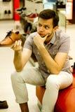 Un type dans le magasin choisit des chaussures Photographie stock