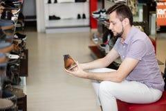 Un type dans le magasin choisit des chaussures Image libre de droits