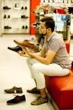 Un type dans le magasin choisit des chaussures Image stock