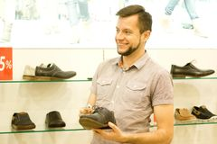 Un type dans le magasin choisit des chaussures Photos libres de droits