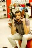 Un type dans le magasin choisit des chaussures J'ai mis mes chaussures sur mon visage, dupé autour Photo stock