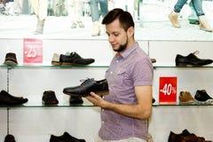Un type dans le magasin choisit des chaussures Vente Photo libre de droits