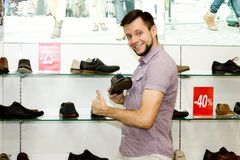 Un type dans le magasin choisit des chaussures Vente Photo stock