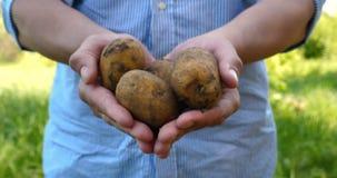 Un type de portrait un agriculteur dans un chapeau de paille, dans la chemise de robe longue creuse une pomme de terre banque de vidéos