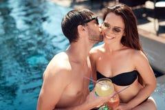 Un type embrasse une fille, s'asseyant ensemble par la piscine Image libre de droits