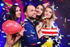 Un type et trois filles se réjouissent et célèbrent la partie dans la boîte de nuit Photos stock