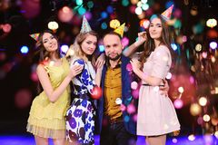 Un type et trois filles se réjouissent et célèbrent la partie dans la boîte de nuit Images stock