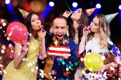 Un type et trois filles se réjouissent et célèbrent la partie dans la boîte de nuit Image stock