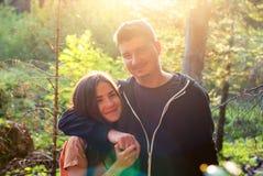 Un type et une étreinte de fille au coucher du soleil dans la forêt Images libres de droits