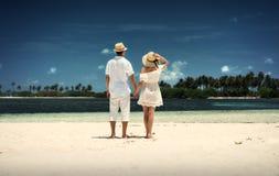 Un type et une fille dans des vêtements blancs sur le rivage de l'île maldives Sable blanc Guraidhoo Photographie stock libre de droits