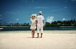 Un type et une fille dans des vêtements blancs sur le rivage de l'île maldives Sable blanc Guraidhoo Vacances Photographie stock