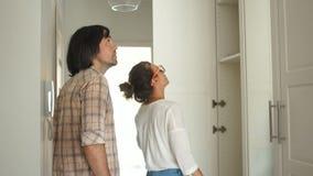 Un type et une fille, une jeune famille inspectent les casiers en leur appartement nouvellement rénové Les jeunes heureux clips vidéos