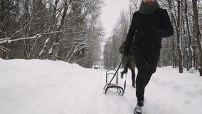 Un type et une fille jouent dans la neige dans l'amusement d'hiver de forêt banque de vidéos