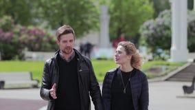 Un type et une fille marchent dans la zone de parc et causent mignon les uns avec les autres Front View banque de vidéos