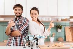 Un type et une fille posent dans une cuisine moderne Est tout près un rhinocéros de robot Ils ont coûté dans la cuisine légère mo Photos stock